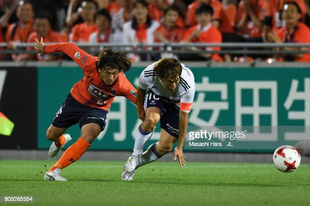 Manabu Saito of Yokohama FMarinos and Takuya Wada of Omiya Ardija compete for the ball during the JLeague J1 match between Omiya Ardija and Yokohama...