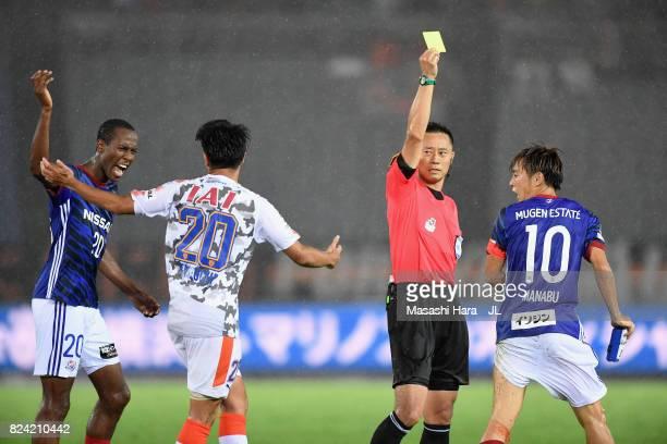 Manabu Saito of Yokohama FMarinos is shown a yellow card by referee Minoru Tojo while Martinus of Yokohama FMarinos and Ryo Takeuchi of Shimizu...