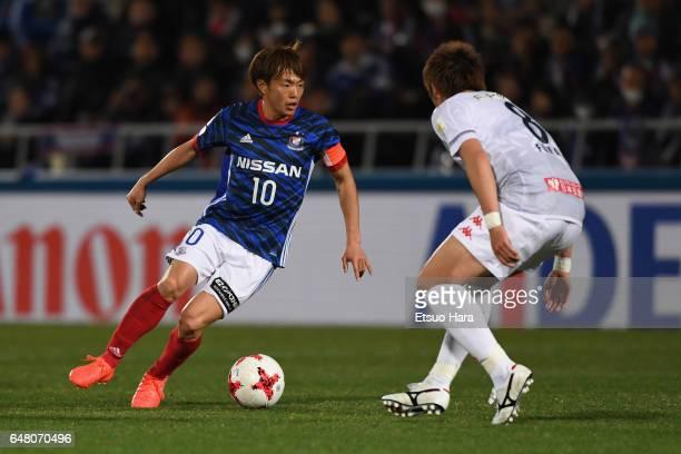 Manabu Saito of Yokohama FMarinos takes on Kazuki Fukai of Consadole Sapporo during the JLeague J1 match between Yokohama FMarinos and Consadole...