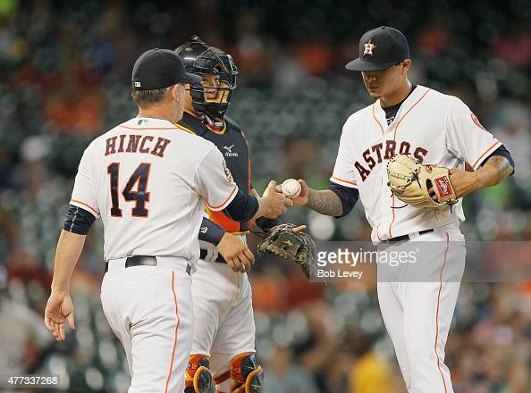 Manager AJ Hinch of the Houston Astros takes the ball from Vincent Velasquez in the fifth inning against the Colorado Rockies as Jason Castro looks...