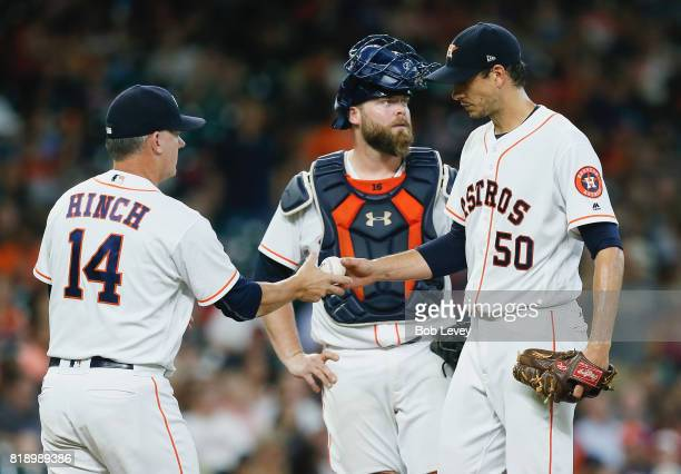 Manager AJ Hinch takes the ball from Charlie Morton in the seventh inning as Brian McCann looks on at Minute Maid Park on July 19 2017 in Houston...
