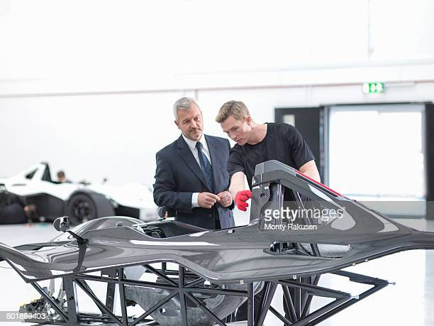 Manager and engineer inspecting carbon fibre body of supercar in sports car factory