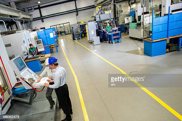 Manager and Female Engineer in the Factory Disscusing Project