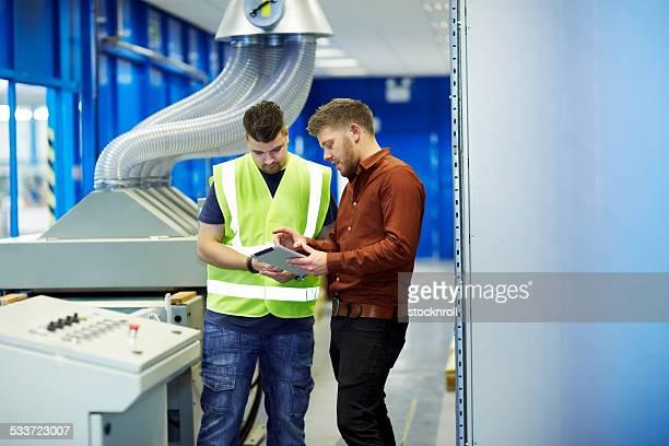 Manager und foreman diskutieren Arbeit mit tablet PC
