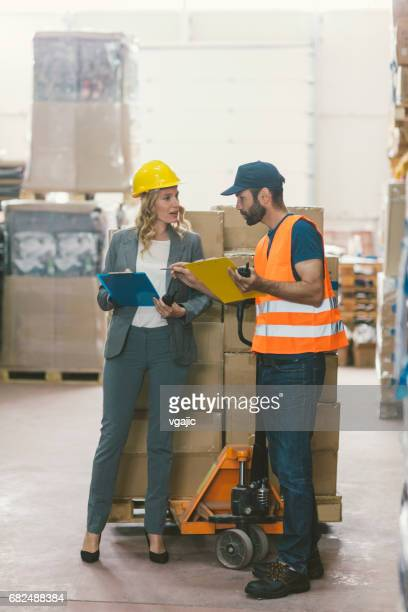 Manager and manual worker in warehouse