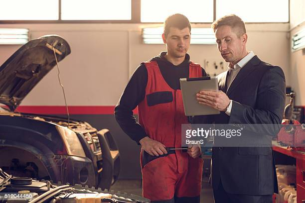 Manager and mechanic working on digital tablet in repair shop.