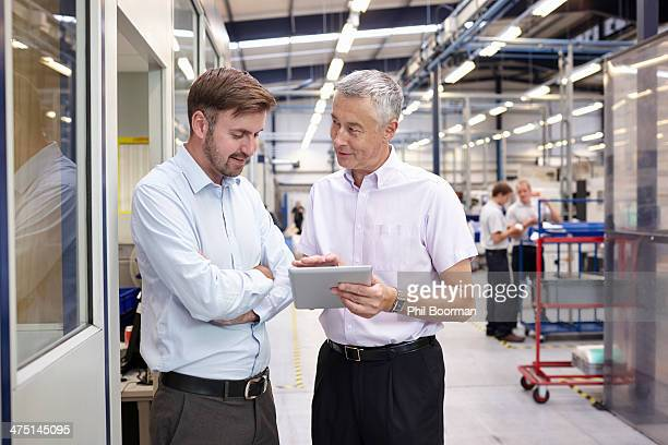 Manager and worker looking at digital tablet in engineering factory