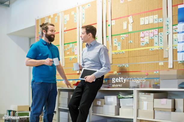 Manager und Arbeiter unter Kaffeepause an Druckmaschine