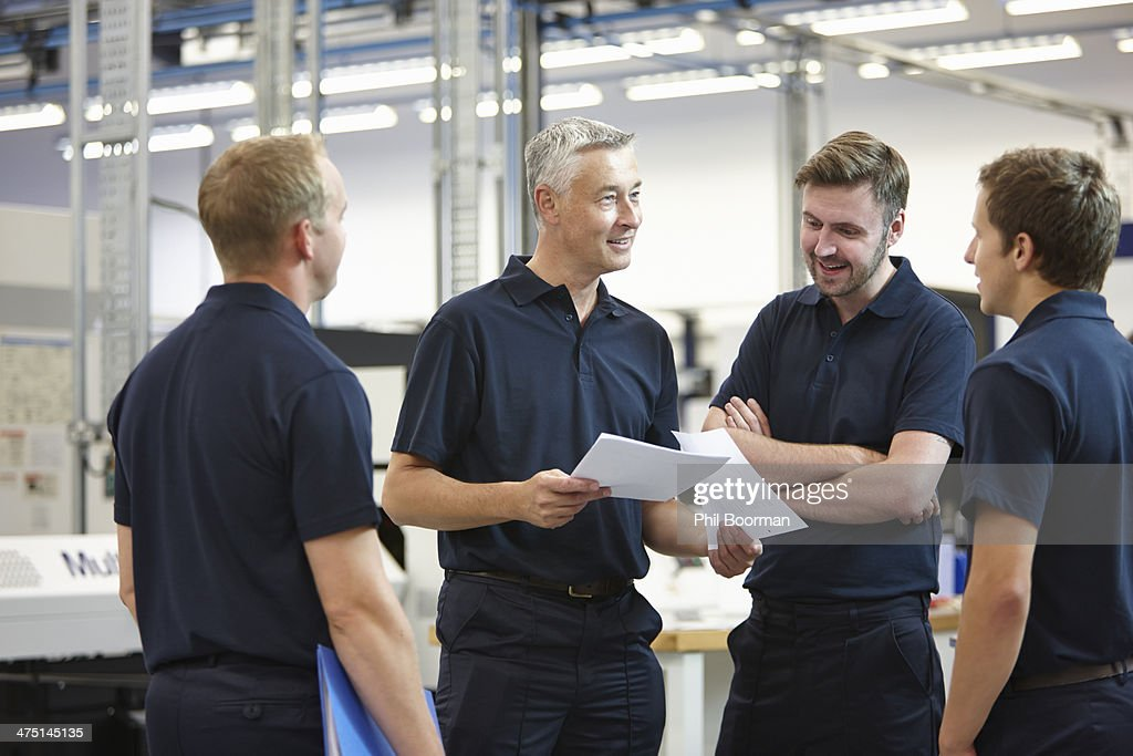 Manager and workers discussing paperwork in engineering factory