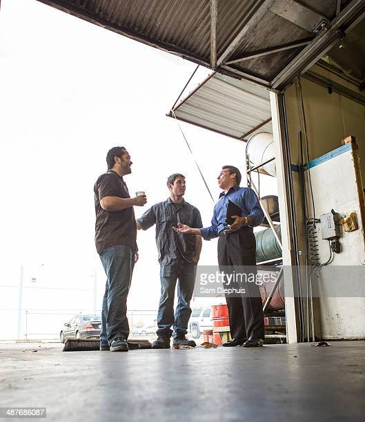 Manager and workers talking at warehouse loading dock