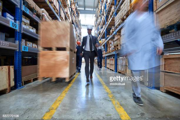 Manager and workers walkingin warehouse aisle