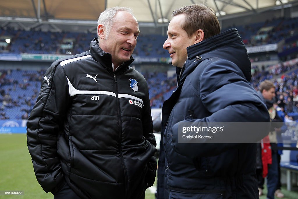 Manager Andreas Mueller of Hoffenheim and manager Horst Heldt of Schalke talk prior to the Bundesliga match between FC Schalke 04 and TSG 1899 Hoffenheim at Veltins-Arena on March 30, 2013 in Gelsenkirchen, Germany.