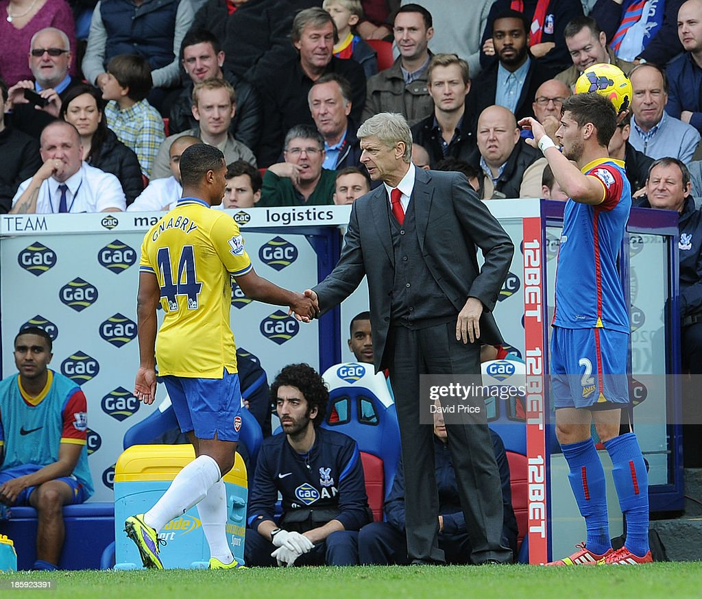 Manager Arsene Wenger of Arsenal shakes hands with Serge Gnabry after is substituted during the Barclays Premier League match between Crystal Palace and Arsenal at Selhurst Park on October 26, 2013 in London, England.