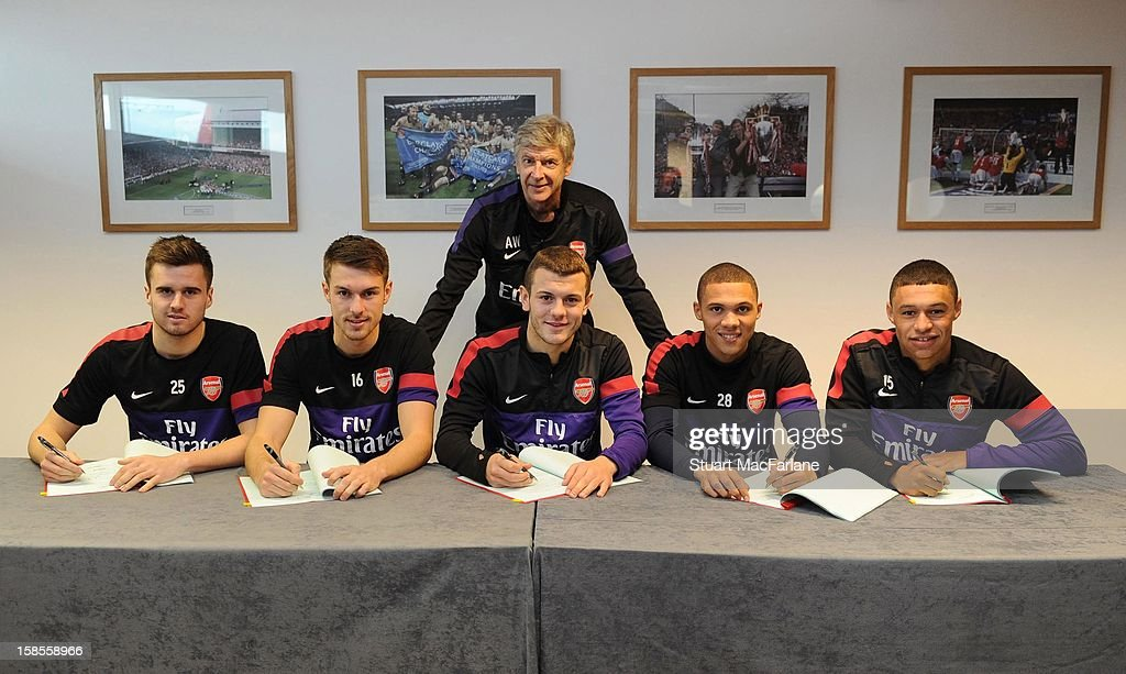 Manager Arsene Wenger of Arsenal stands over (L-R) Carl Jenkinson, Aaron Ramsey, Jack Wilshere, Kieran Gibbs and Alex Oxlade-Chamberlain of Arsenal as they each sign their new longterm contracts at London Colney on December 19, 2012 in St Albans, England.
