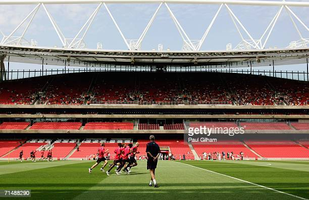 Manager Arsene Wenger of Arsenal watches his players warm up during an Arsenal Training and Emirates Stadium Open Day at the Emirates Stadium on July...