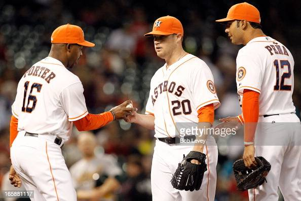 Manager Bo Porter of the Houston Astros takes the ball from Bud Norris of the Astros as he leaves the game in the sixth inning while teammate Carlos...