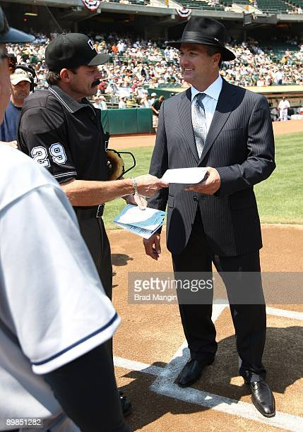 Manager Bob Geren of the Oakland Athletics hands his lineup card to home plate umpire Bill Hohn at home plate before the game against the Chicago...