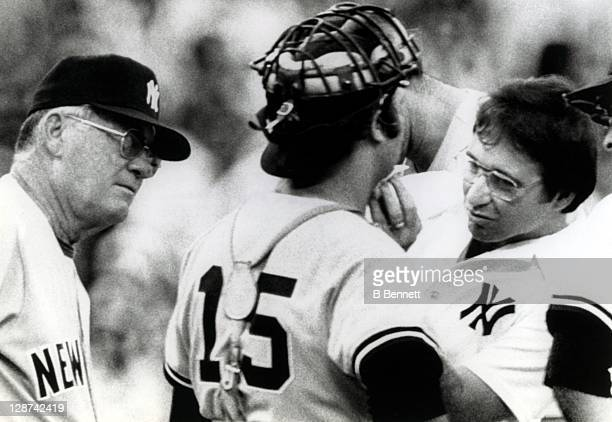 Manager Bob Lemon of the New York Yankees looks on as trainer Gene Monahan repairs the cut on the chin of catcher Thurman Munson after he was...