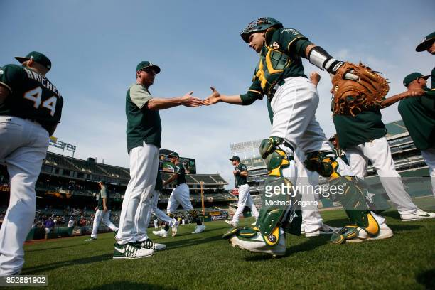 Manager Bob Melvin and Dustin Garneau of the Oakland Athletics celebrate on the field following the game against the Los Angeles Angels of Anaheim at...