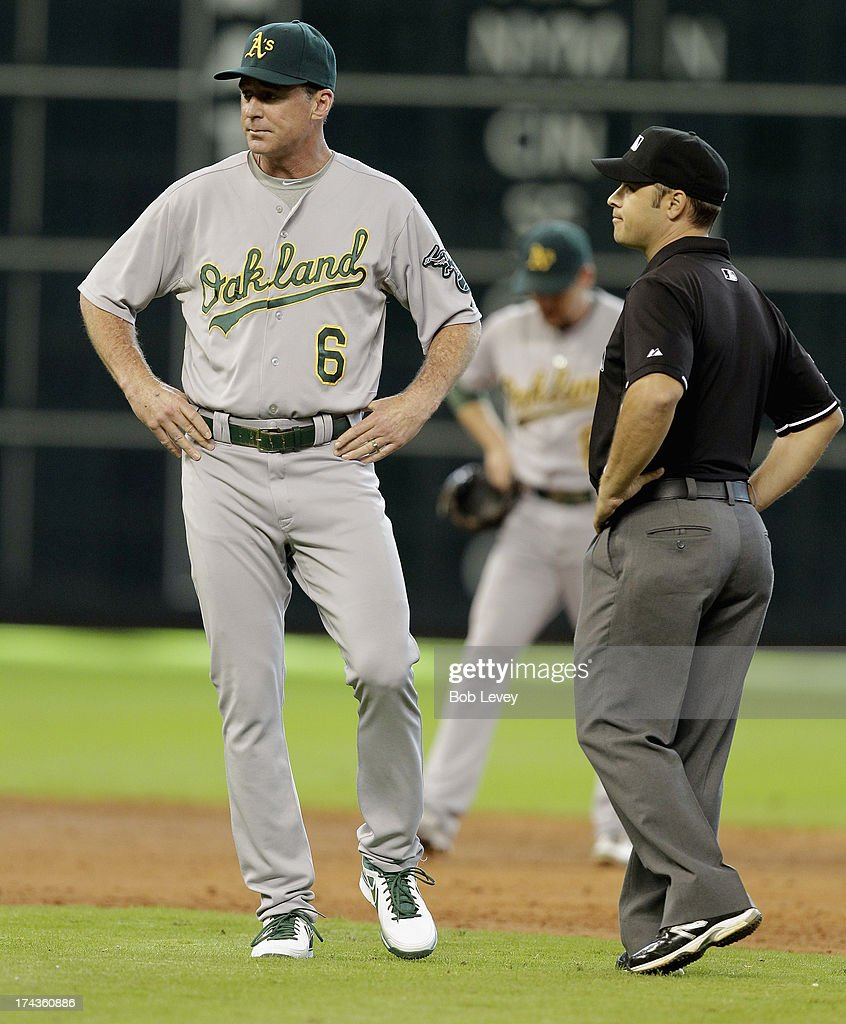 Manager Bob Melvin #6 of the Oakland Athletics argues with second base umpire Mark Wegner as to whether Jose Altuve of the Houston Astros was safe on a steal attempt at Minute Maid Park on July 24, 2013 in Houston, Texas.