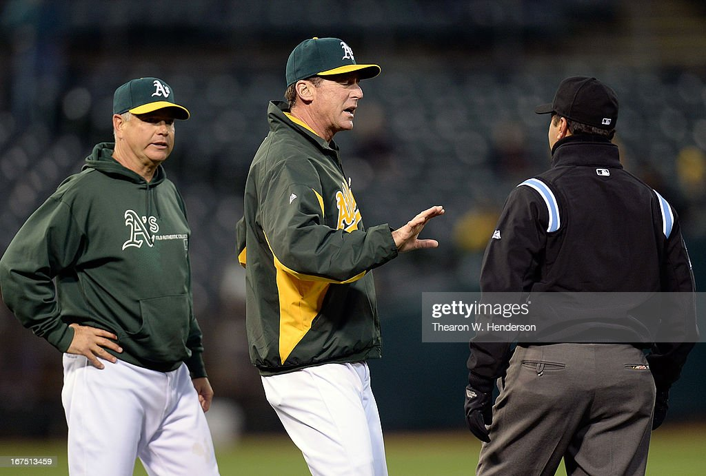 Manager Bob Melvin (C) of the Oakland Athletics seperates his pitching coach Curt Young (L) from arguing with first base umpire Jim Reynolds (R) in the third inning during a MLB game against the Baltimore Orioles at O.co Coliseum on April 25, 2013 in Oakland, California.