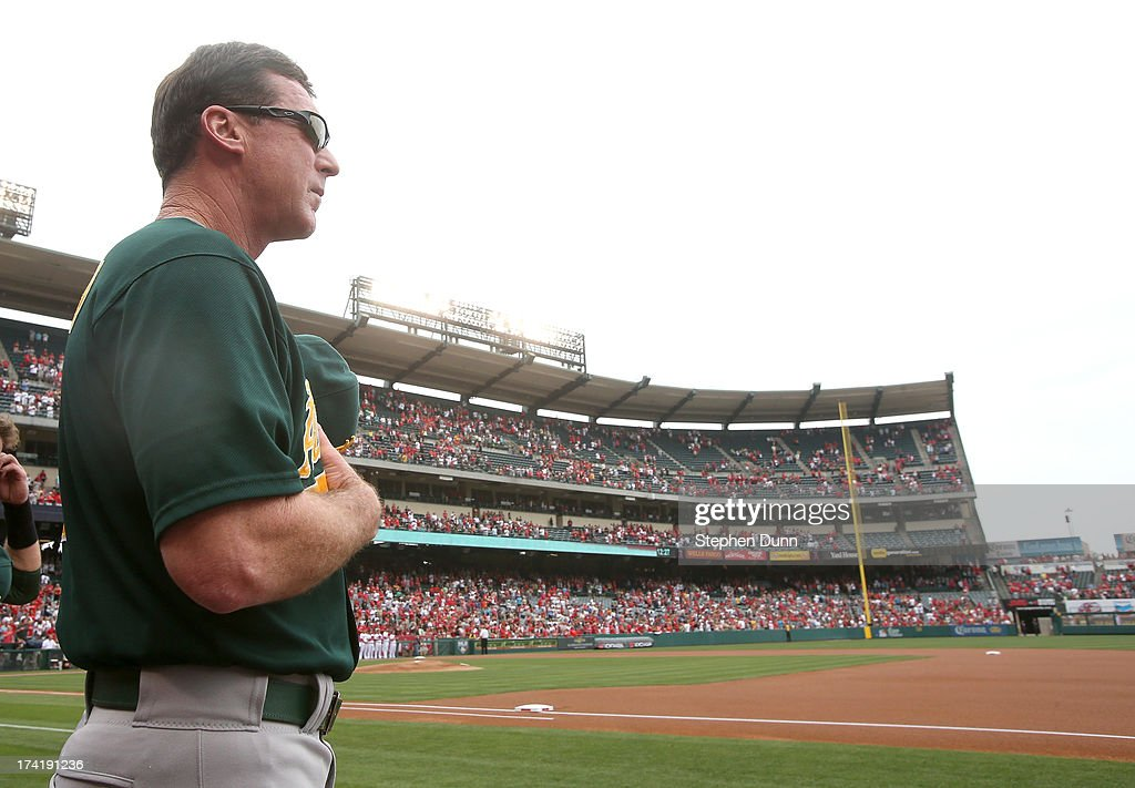 Manager Bob Melvin of the Oakland Athletics stands by the dugout for the national anthem before the game against the Los Angeles Angels of Anaheim at Angel Stadium of Anaheim on July 21, 2013 in Anaheim, California.