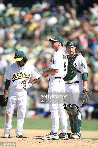 Manager Bob Melvin of the Oakland Athletics stands on the mound with Jemile Weeks and Landon Powell waiting for the new pitcher during the game...