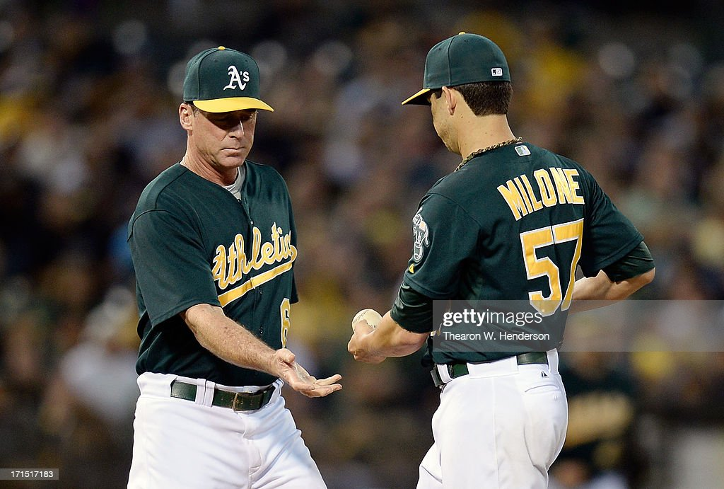 Manager Bob Melvin #6 of the Oakland Athletics takes the ball from Tommy Milone #57 taking him out of the game after Milone walked in a run with the bases loaded and two outs in the fifth inning against the Cincinnati Reds at O.co Coliseum on June 25, 2013 in Oakland, California.