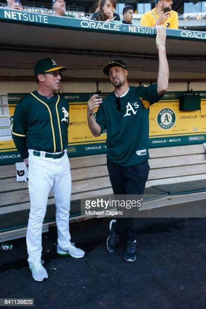 Manager Bob Melvin of the Oakland Athletics talks with Klay Thompson of the Golden State Warrios in the dugout prior to during the game against the...