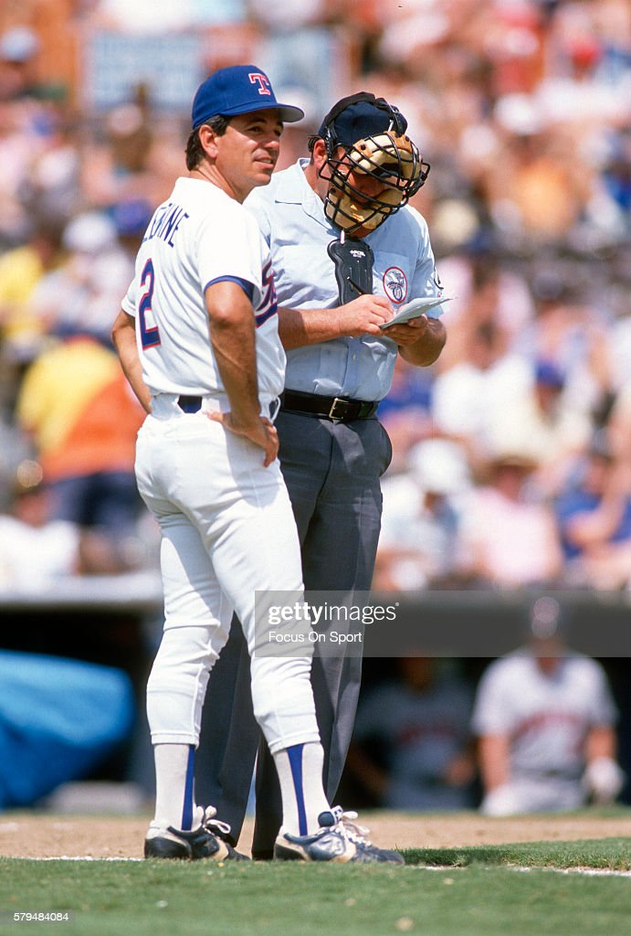 Manager Bobby Valentine of the Texas Rangers gives a change in his lineup to the home plate umpire during an Major League Baseball spring training...