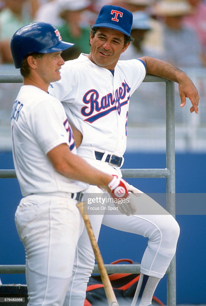 Manager Bobby Valentine of the Texas Rangers talks with one of his players in the dugout during an Major League Baseball spring training game circa...