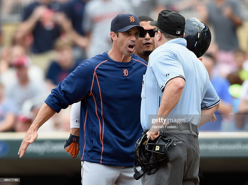 Manager Brad Ausmus #7 of the Detroit Tigers gets between Victor Martinez #41 and home plate umpire Marty Foster #60 after Martinez was ejected during the fifth inning of the game against the Minnesota Twins on July 11, 2015 at Target Field in Minneapolis, Minnesota.