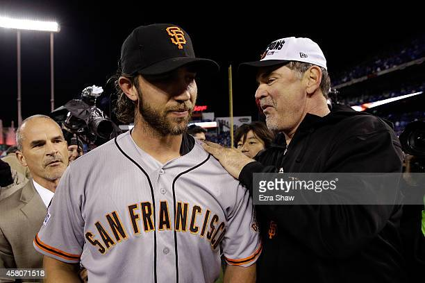 Manager Bruce Bochy of the San Francisco Giants celebrates on the field with Madison Bumgarner after defeating the Kansas City Royals 32 to win Game...