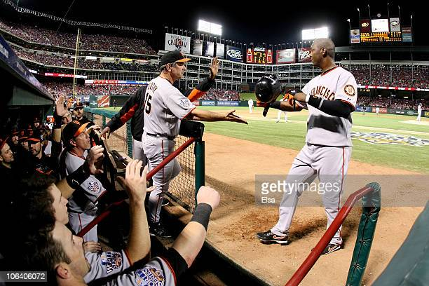 Manager Bruce Bochy of the San Francisco Giants congratulates Edgar Renteria after Renteria scored in the top of the seventh inning against the Texas...