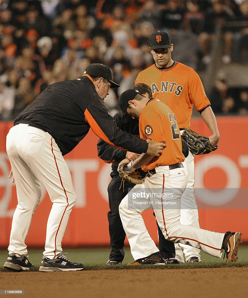 Manager <a gi-track='captionPersonalityLinkClicked' href=/galleries/search?phrase=Bruce+Bochy&family=editorial&specificpeople=220291 ng-click='$event.stopPropagation()'>Bruce Bochy</a> (L) of the San Francisco Giants helps injured second baseman <a gi-track='captionPersonalityLinkClicked' href=/galleries/search?phrase=Freddy+Sanchez&family=editorial&specificpeople=220611 ng-click='$event.stopPropagation()'>Freddy Sanchez</a> #21 up and off the field as <a gi-track='captionPersonalityLinkClicked' href=/galleries/search?phrase=Pat+Burrell&family=editorial&specificpeople=213091 ng-click='$event.stopPropagation()'>Pat Burrell</a> #5 looks on against the Cincinnati Reds during a MLB baseball game June 10, 2011 at AT&T Park in San Francisco, California.