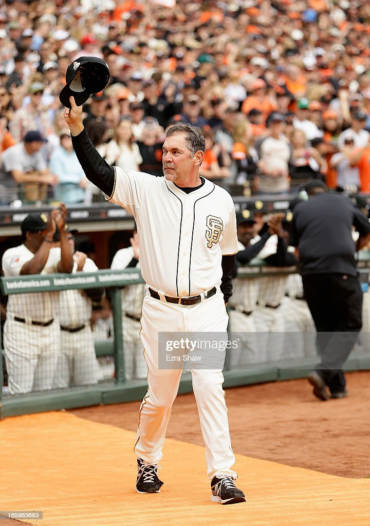 Manager Bruce Bochy #15 of the San Francisco Giants waves to the crowd as he walks on to the field to receive his 2012 Championship Ring during a pregame ceremony honoring the 2012 World Series champions before their game against the St. Louis Cardinals at AT&T Park on April 7, 2013 in San Francisco, California.