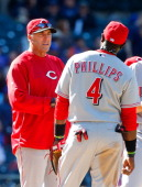 Manager Bryan Price of the Cincinnati Reds stands on the mound with Brandon Phillips during a pitching change against the New York Mets at Citi Field...