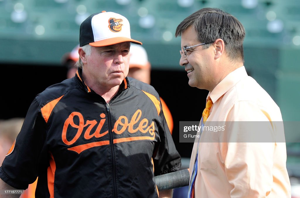 Manager <a gi-track='captionPersonalityLinkClicked' href=/galleries/search?phrase=Buck+Showalter&family=editorial&specificpeople=208183 ng-click='$event.stopPropagation()'>Buck Showalter</a> #26 and General Manager Dan Duquette of the Baltimore Orioles talk before the game against the Colorado Rockies at Oriole Park at Camden Yards on August 16, 2013 in Baltimore, Maryland.