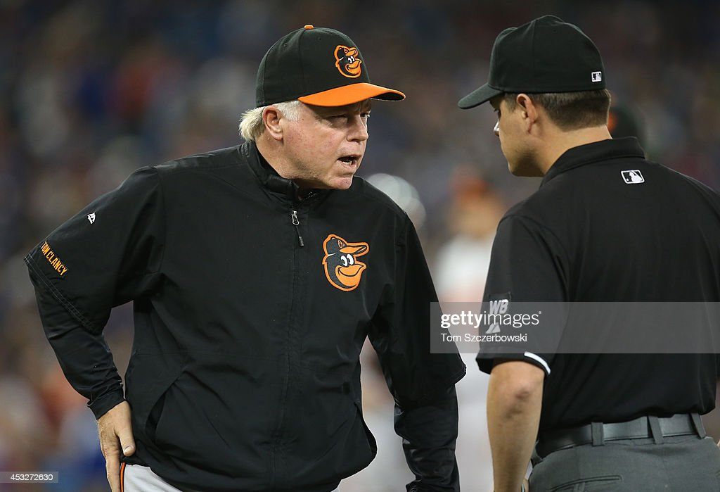 Manager <a gi-track='captionPersonalityLinkClicked' href=/galleries/search?phrase=Buck+Showalter&family=editorial&specificpeople=208183 ng-click='$event.stopPropagation()'>Buck Showalter</a> #26 of the Baltimore Orioles talks to first base umpire D.J. Reyburn #70 to challenge a call in the eighth inning during MLB game action against the Toronto Blue Jays on August 6, 2014 at Rogers Centre in Toronto, Ontario, Canada.