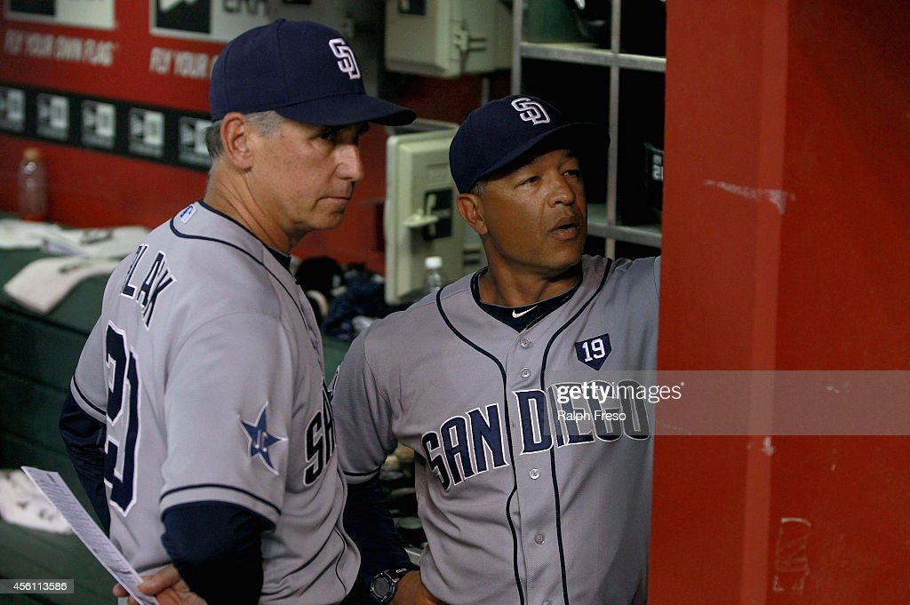 Manager Bud Black of the San Diego Padres and bench coach Dave Roberts of the Padres look over the roster during the seventh inning of a MLB game...