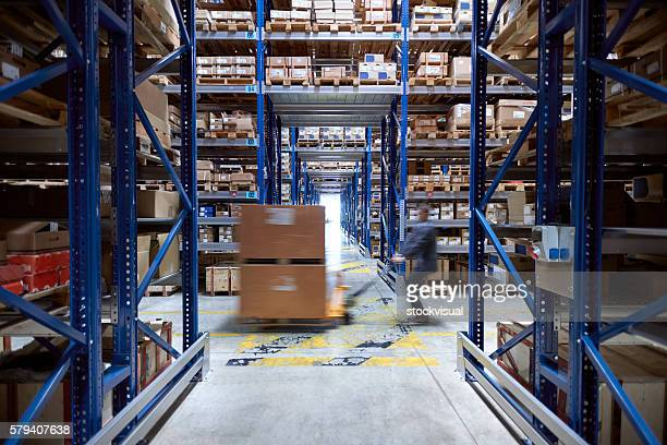Manager carrying wooden box in warehouse.