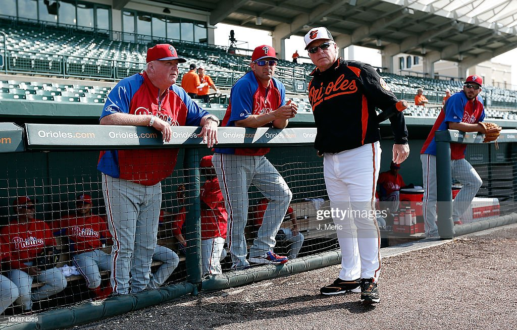Manager Charlie Manuel #41 (L) of the Philadelphia Phillies talks with manager Buck Showalter #26 of the Baltimore Orioles as Michael Young #10 of the Phillies looks on just before the start of the Grapefruit League Spring Training Game at Ed Smith Stadium on March 23, 2013 in Sarasota, Florida.