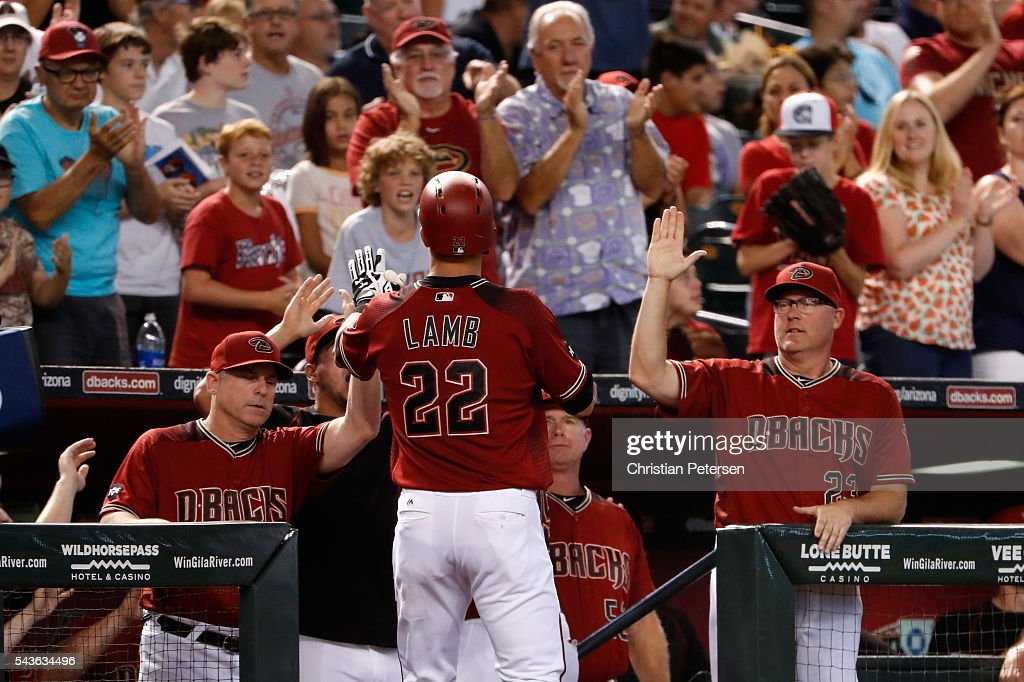 Manager Chip Hale #3 and pitching coach Mike Butcher #23 of the Arizona Diamondbacks high-five Jake Lamb #22 after hitting a three-run home run against the Philadelphia Phillies during the first inning of the MLB game at Chase Field on June 29, 2016 in Phoenix, Arizona.