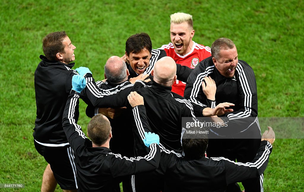 Manager Chris Coleman (C) and Wales team staffs celebrate their team's 3-1 win with <a gi-track='captionPersonalityLinkClicked' href=/galleries/search?phrase=Aaron+Ramsey+-+Soccer+Player&family=editorial&specificpeople=4784114 ng-click='$event.stopPropagation()'>Aaron Ramsey</a> (R) after the UEFA EURO 2016 quarter final match between Wales and Belgium at Stade Pierre-Mauroy on July 1, 2016 in Lille, France.
