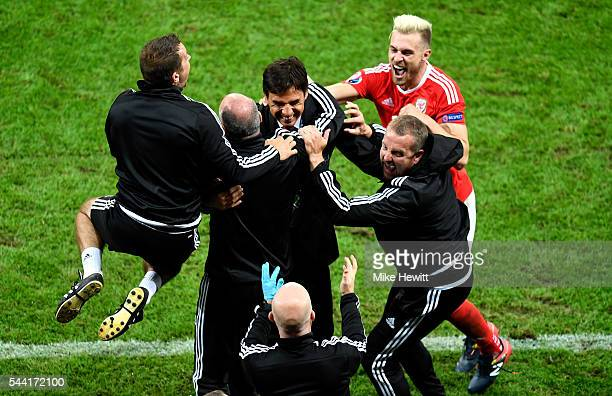 Manager Chris Coleman and Wales team staffs celebrate their team's 31 win with Aaron Ramsey after the UEFA EURO 2016 quarter final match between...