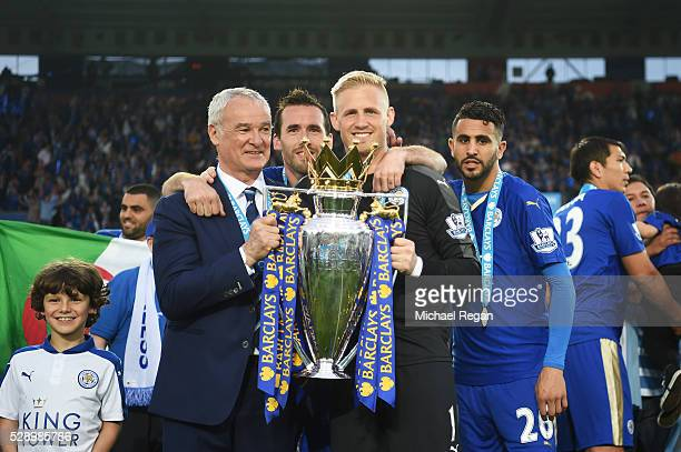Manager Claudio Ranieri Christian Fuchs Kasper Schmeichel and Riyad Mahrez of Leicester City pose with the Premier League Trophy as players and...