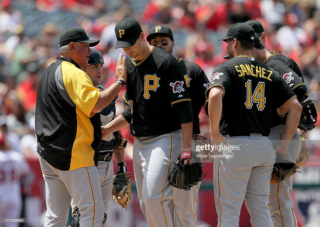 Manager Clint Hurdle #13 of the Pittsburgh Pirates pats pitcher Charlie Morton #50 on the shouldder after pulling Morton from the game in the sixth inning during the MLB game againt the Los Angeles Angels of Anaheim at Angel Stadium of Anaheim on June 23, 2013 in Anaheim, California.