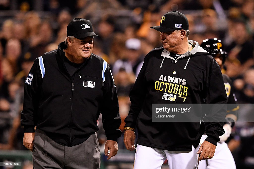 Manager Clint Hurdle of the Pittsburgh Pirates talks to first base umpire Joe West about a replay in the fourth inning during the National League...
