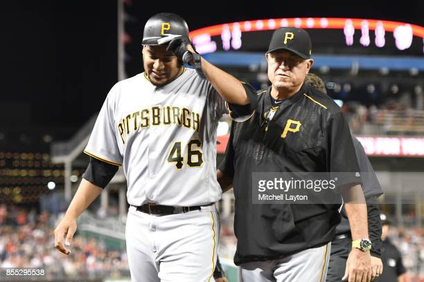 Manager Clint Hurdle of the Pittsburgh Pirates walks off Ivan Nova from the game after foul tipping a ball off his hand in the this inning during a...