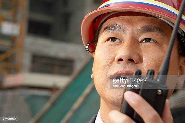 A manager communicates by walkie-talkie at the construction site.